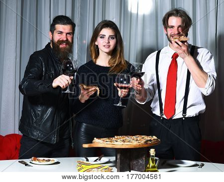 Happy friends pretty girl and two bearded men hipsters with beards toasting glasses with red wine and eating tasty pizza at party in pizzeria cafe or restaurant