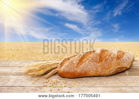 long loaf on wooden table with golden field on the background. Fresh baked traditional bread on nature background. Ripe cereal field, blue sky with beautiful clouds and sun