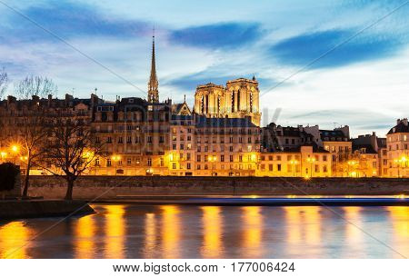 Embankment of the Seine near the Ile de la Cite at night Notre Dame in the background Paris France