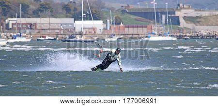 kitesurfer riding board toeside in Portland harbour