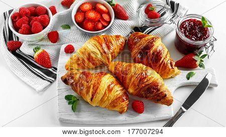 Fresh tasty homemade croissants with ripe berries and raspberries jam on white wooden board.