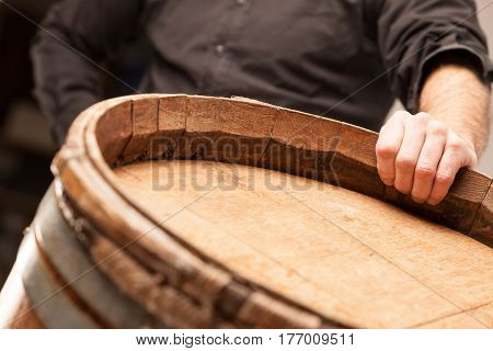 Man Standing With His Hand On An Oak Barrel