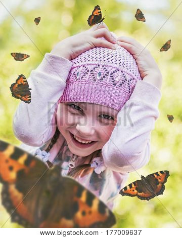 Enthusiastic little girl is surrounded by flying butterflies on a summer day.