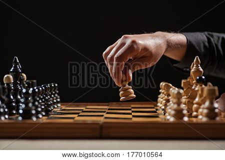 Close up image of man who is making first move in chess game.