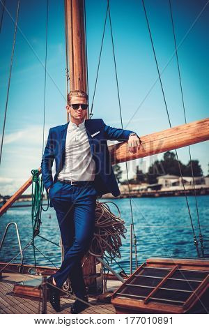Stylish wealthy man on a luxury wooden regatta.