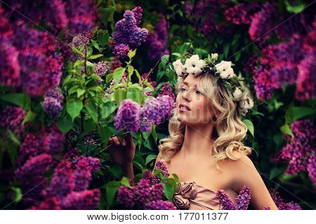 Spring Model Girl with Long Bob Hairstyle. Glamour Woman with Blonde Wavy Hair on Flowers Background