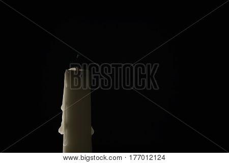 extinguished candle over black background, simple photo