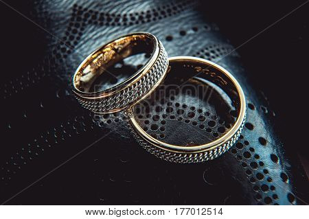 unusual luxery wedding rings on the dark perforated leather of a shue