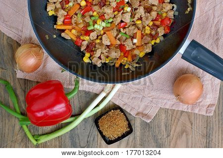 Ragout From Pork Meat, Red Pepper, Onion, Spring Onion, Carrot And Spices In Black Pan On Grey Cloth