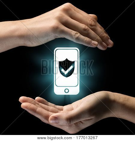 Isolated image of two hands on black background. Smartphone icon with shield in the center as a symbol of security data protection. Concept of security data protection.