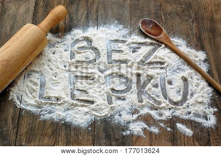Gluten Free Flour With Text Gluten Free In Czech Language With Wooden Spoon And Rolling Pin On Dark