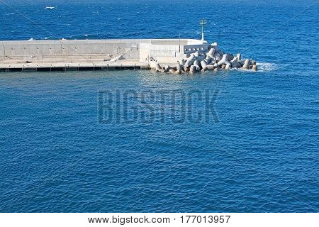 Stone jetty and blue ocean on a sunny day in Mallorca Balearic islands Spain.