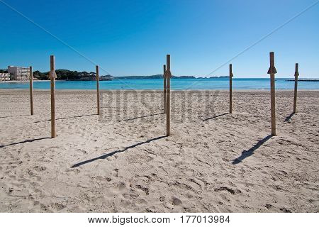 Spring beach sunshine and ocean with beach poles in Mallorca Spain.