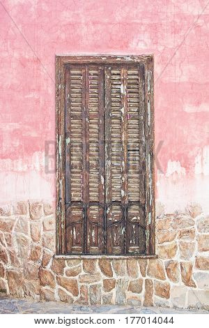 Brown wood window shutters on pink roughcast and stone wall in Mallorca Spain.