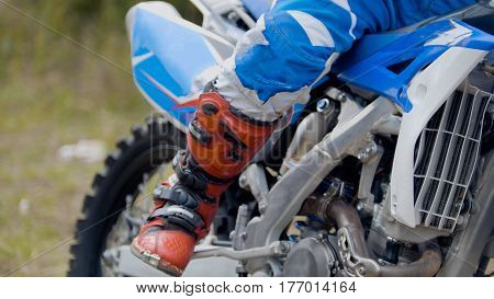 Close up view of boots MXgirl on dirtbike - motocross sport, telephoto