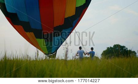 Crew inflate a colored hot air balloon at summer field, wide angle