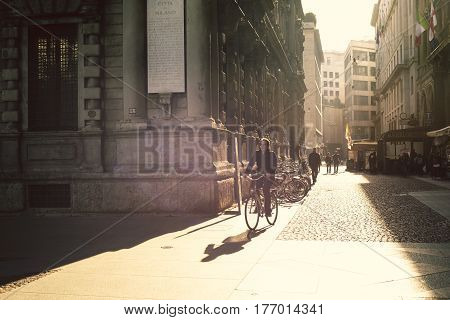 MILAN - OCTOBER 22: Man rides bicycle by cobblestone pavement along sunny street by morning in Milan Italy on October 22 2015.