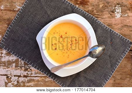 Soup From Pumpkin And Coconut Milk In White Bowl With Spoon On Grey Cloth On Rustic Table