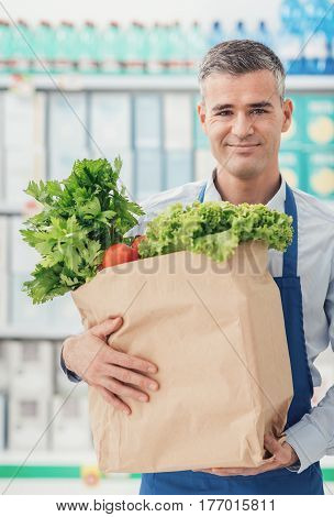 Shop Assistant Holding A Grocery Bag