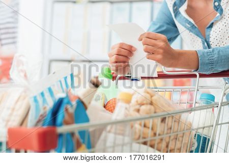 Woman doing grocery shopping at the supermarket she is pushing a cart and checking a list