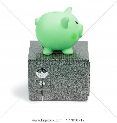 Green ceramic piggy bank standing on a safe isolated on white background. Ecology investment money for sustainable green energy saving on costs save the Earth concept.