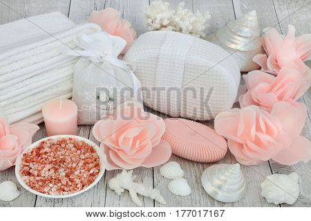 Skincare ex foliating and detoxifying beauty treatment with himalayan sea salt, rose flower soap petals, bathroom accessories and shells.