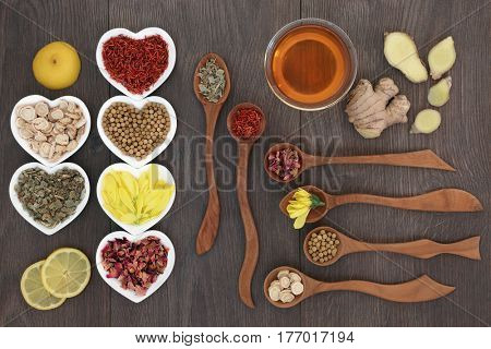Medicinal chinese herb tea selection in heart shaped bowls and wooden spoons with glass tea cup