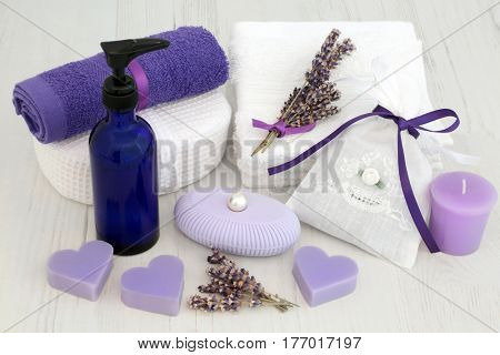 Lavender flowers for cleansing treatment, with moisturising cream, soap, face towels, cloth sponge, fragrant herb bag and candle.