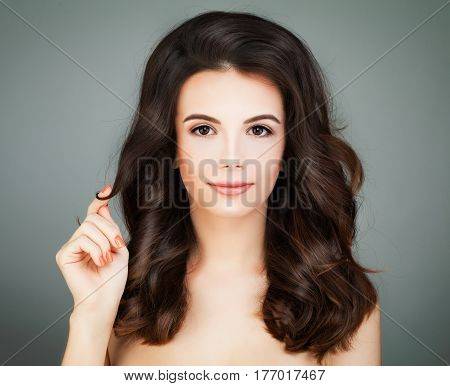 Beautiful Woman with Healthy Hair and Clear Skin touching her Hair. Haircare Concept