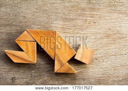 Wooden tangram puzzle in man crouch shape background