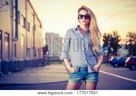 Trendy Hipster Girl in the City at Sunset. Woman in Denim Shorts and Sunglasses. Urban Fashion in Summer Concept. Toned and Filtered Photo. Copy Space.