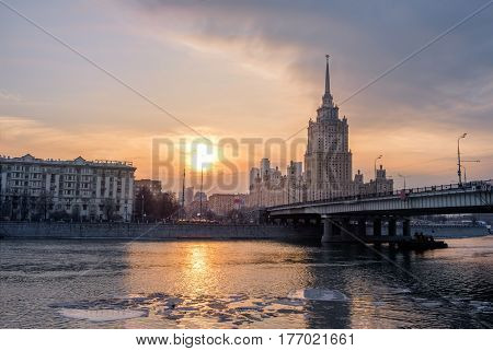 Evening city landscape with sun over the moscow river at sunset with Stalin Skyscraper and its reflection, outdoor travel background, Moscow, Russia