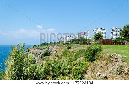 Modern high-rise building on high steep sea shore on blue sky background