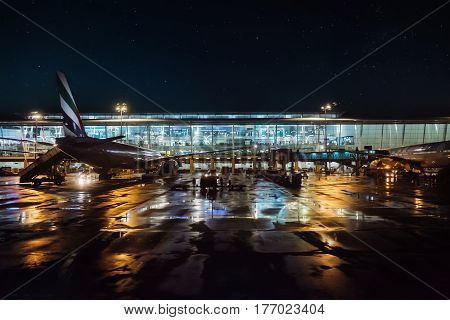 Airplane parked in airport at night dusk waiting for departure with control tower