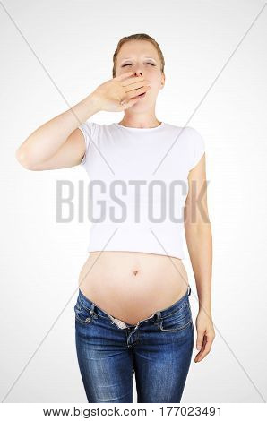 Tired yawning pregnant young woman wearing jeans and a white crop top.