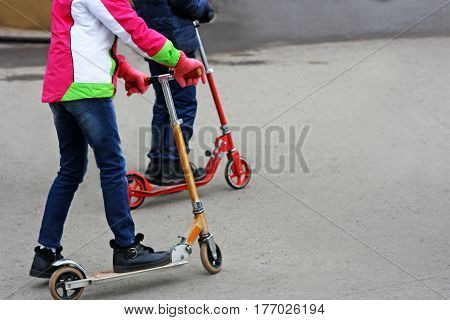 Two teenagers ride on Kick scooter by asphalt road.
