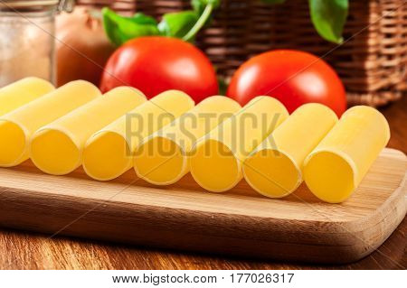 Uncooked Cannelloni Pasta On Cutting Board And Ingredients