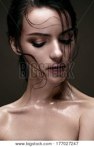 A young girl with shining wet skin and wet hair on her face. Beautiful model with creative bright make-up. Beauty of the face. Photo is made in the studio