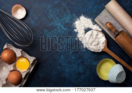 Ingredients and utensils for baking. Spoon with flour eggs rolling pin baking paper whisk for whipping on a blue background. Top view selective focus copy space
