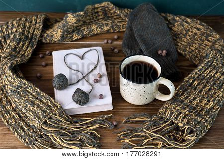 Winter still life with coffee, scarf, mittens, yarn and book on a wooden table.