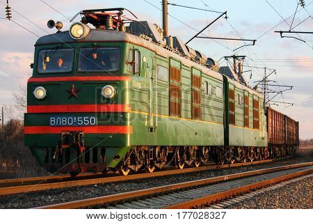 Old electric locomotive with freight train Bataisk Russia 7 February 2012