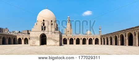 Courtyard of Ibn Tulun Mosque Cairo Egypt. View showing the ablution fountain minaret and minarets of adjoining mosques. The mosque is the largest in the city and the oldest with its original form