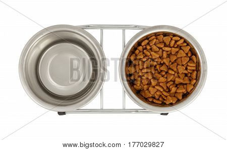 Two metal bowls for dogs and cats on a stand. View from above. One bowl is filled with fodder the second - with water.