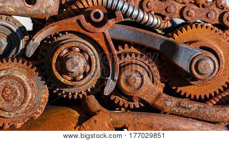 Part of the old mechanism with metal gears sprockets chain and other parts covered with rust.