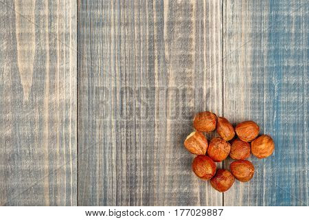 A pile of peeled hazelnuts lies on a wooden background