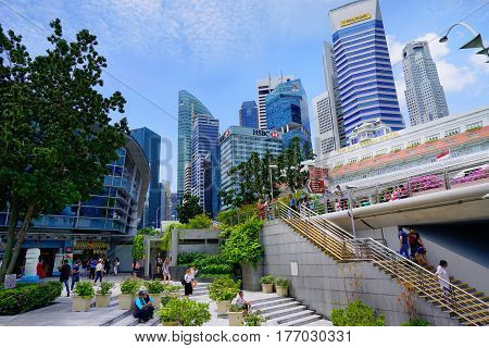 Singapore, Singapore - February 11, 2017: People walk and relax near skyscrapers at the Downtown district on sunny day in Singapore.