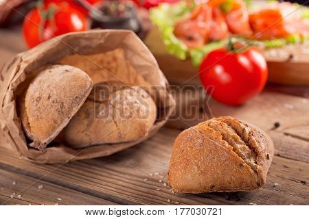 Multigrain bread with slices of smoked salmon chile pepper and tomatoes on rustic wooden background.