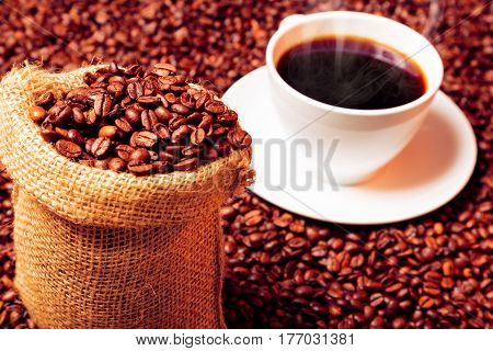 coffee beans in burlap bag and steaming coffee cup