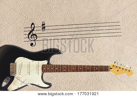 Notes stave and solid body classic electric guitar at the bottom of the light skin background.