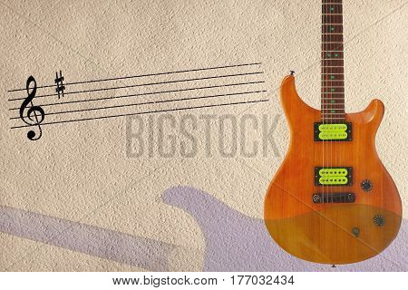 Stave and mahogany wood electric guitar and back of guitar body on the right side of the rough cardboard background.